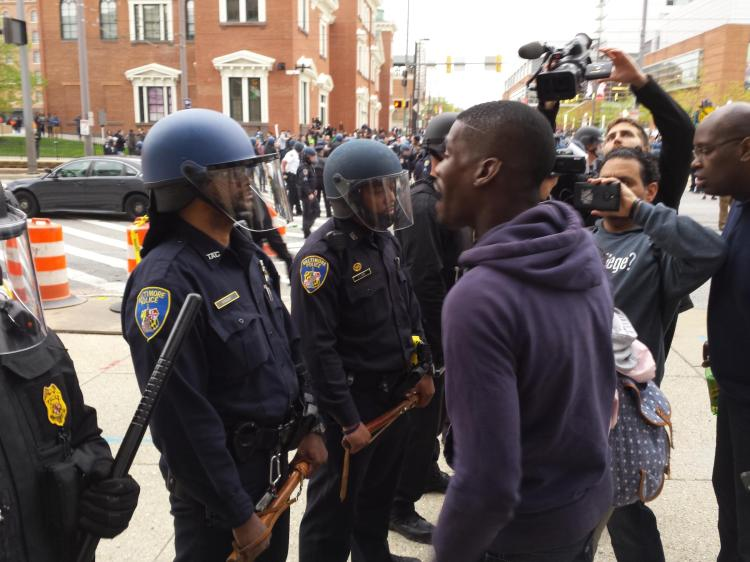A protester screaming at a Baltimore Police officer after protests in the wake of Freddie Gray's death. This moment - from April 25, 2015 - was after protesters and police clashed near Camden Yards.